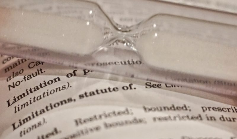 """Image of document with the word """"limitation"""" and a sand timer on top"""