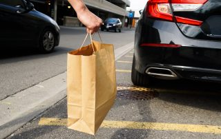 Image of delivery driver holding take-out bag by car