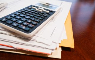 Image of stack of envelopes representing medical expenses with a calculator on top